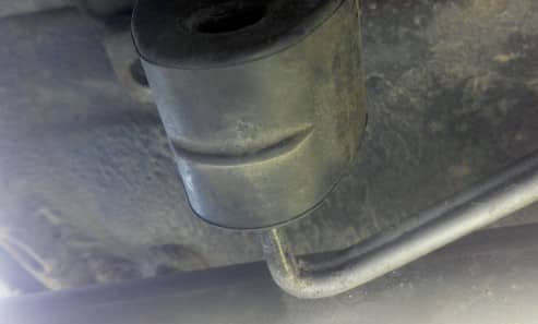 Connecting the hanger of a new exhaust pipe end to a rubber exhaust hanger.