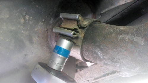 Removing a bolt on an exhaust clamp with a socket and a ratchet.